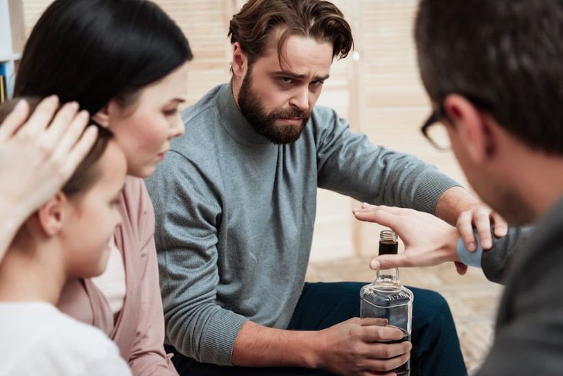 Adult bearded man treats alcoholism in psychologist's office.