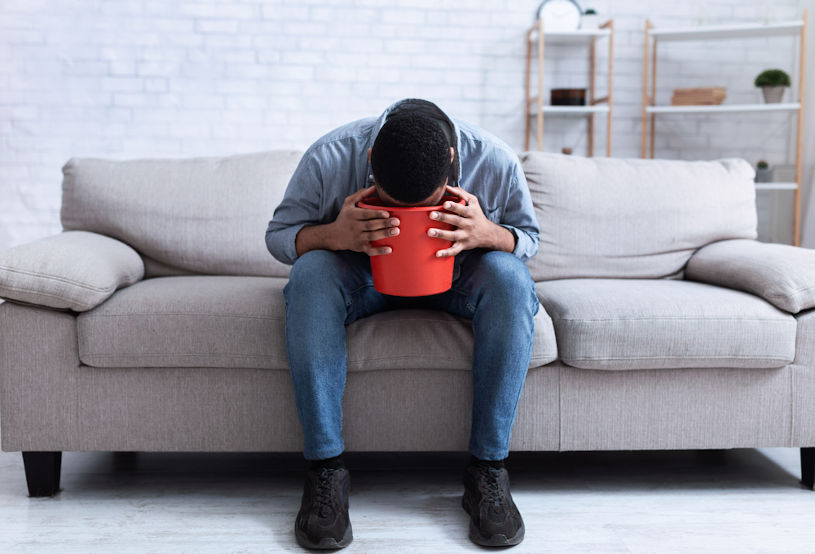 African American Man Vomiting Into A Bucket.