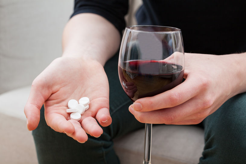 A man is holding pills and alcohol.