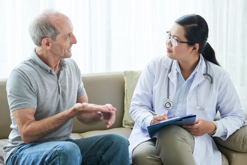 Elderly man sharing complaints with doctor.