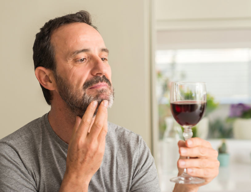 Man drinking a glass of wine.
