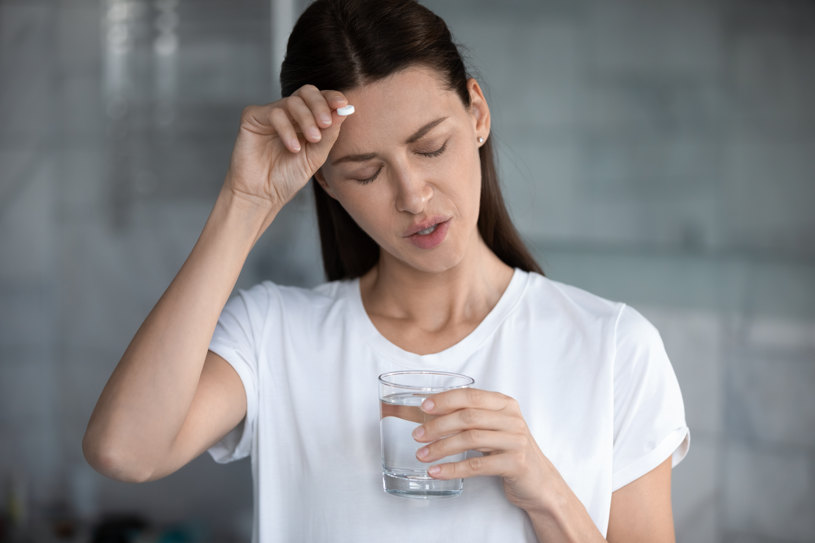 A woman is holding a pill in her hand.
