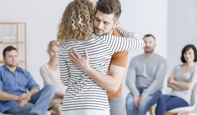 People hugging during support group meeting.
