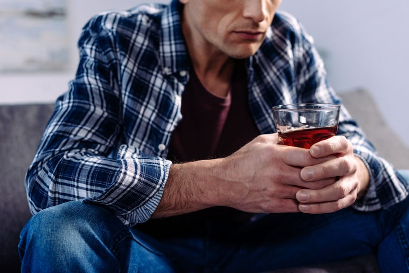 Man sitting with an alcoholic drink.
