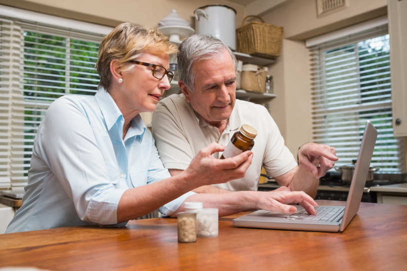 A husband and wife read about Benadryl interactions on their laptop.