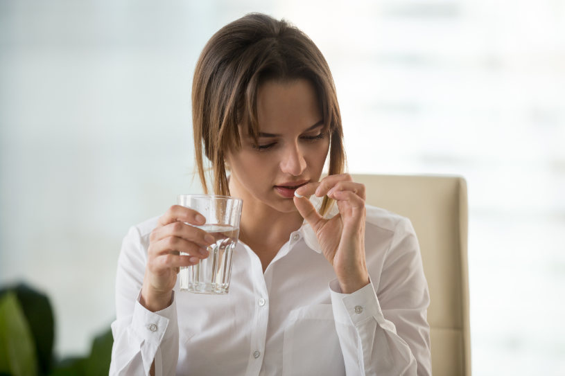Young woman taking pill to relieve headache or illness symptoms.