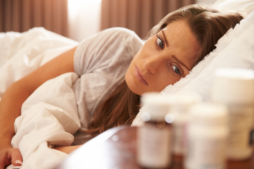 An unhappy woman lies in bed and suffers from Lexapro addiction.