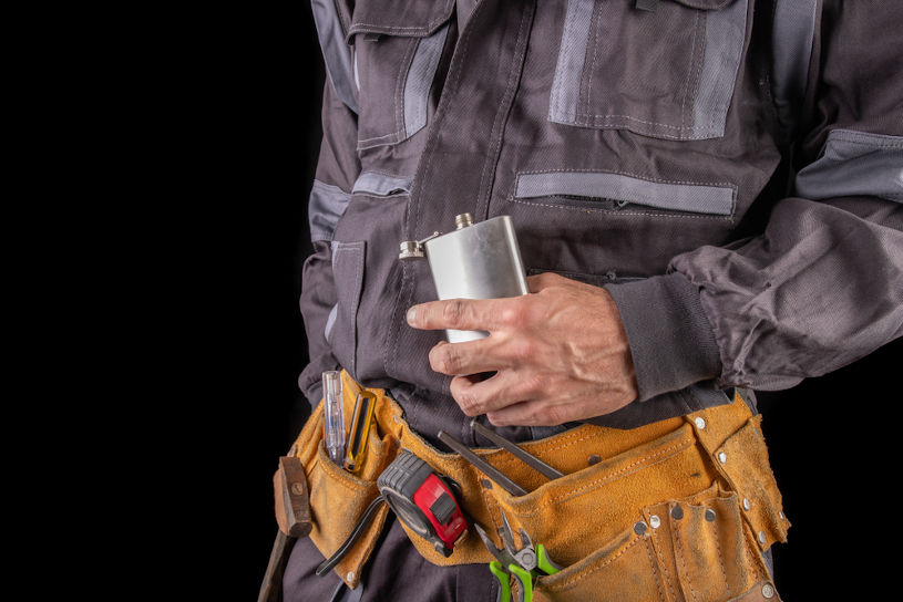 A worker in protective clothing and a flask with alcohol.