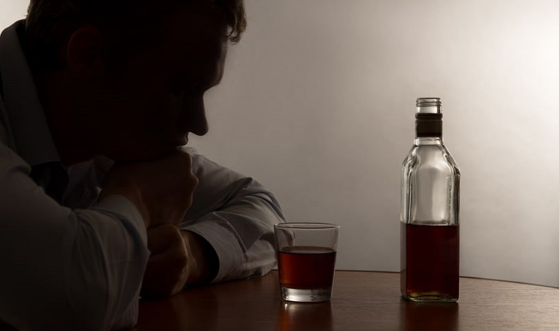 Man addicted to alcohol looking at the bottle.