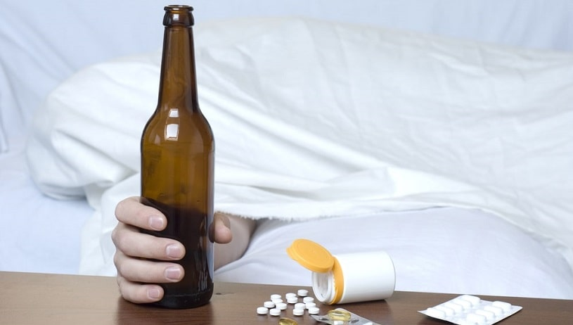 Beer bottle and valium pills on the table.