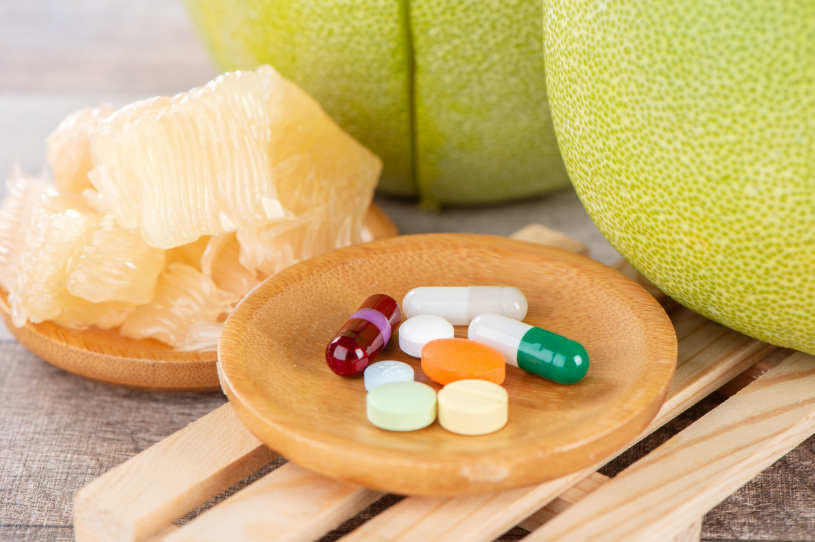 Benadryl pills lie on the table with grapefruit.