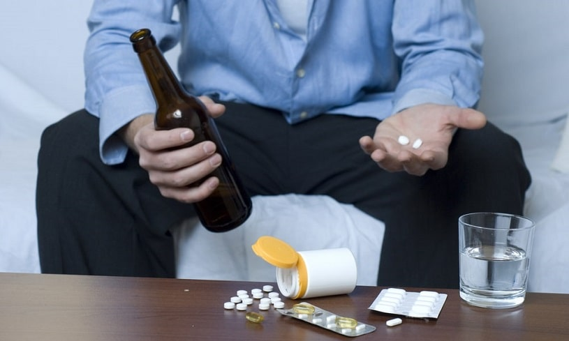 Man sitting on the couch with alcohol and blood thinners on the table and in hands.