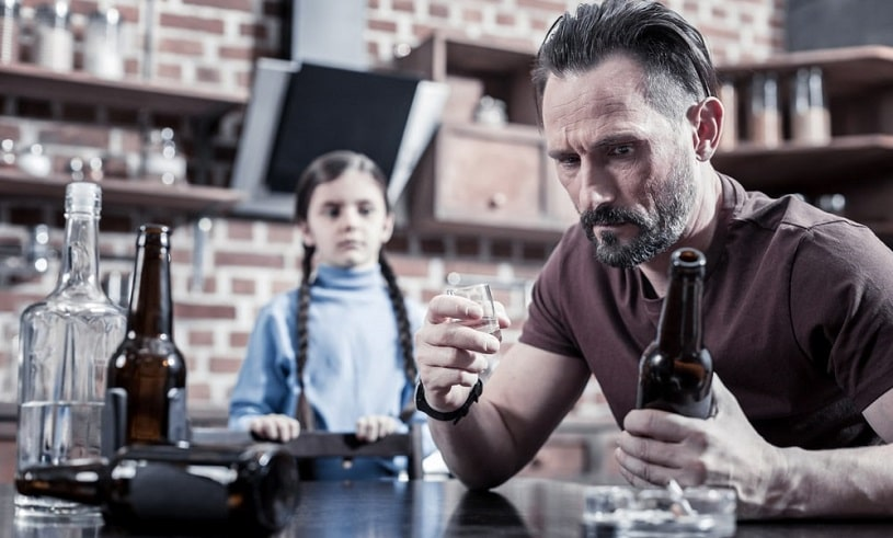 Child looking at the father drinking alcohol.