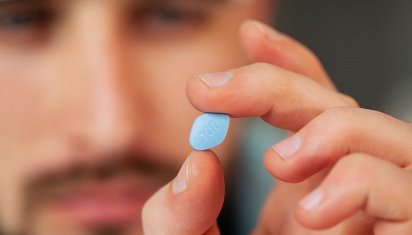 Man holding a viagra pill, close up.