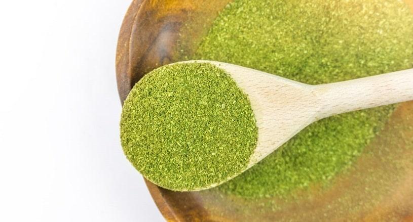 Kratom powder in a wooden spoon.
