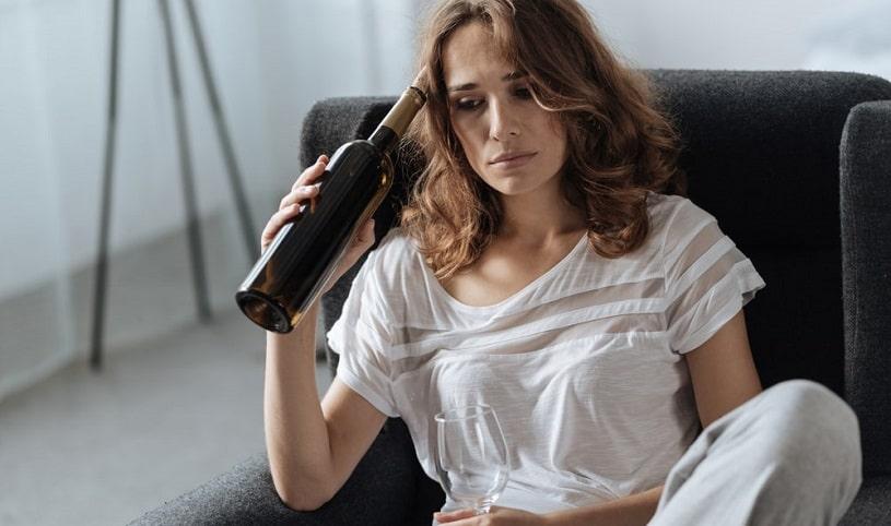 Addicted woman drinking wine.