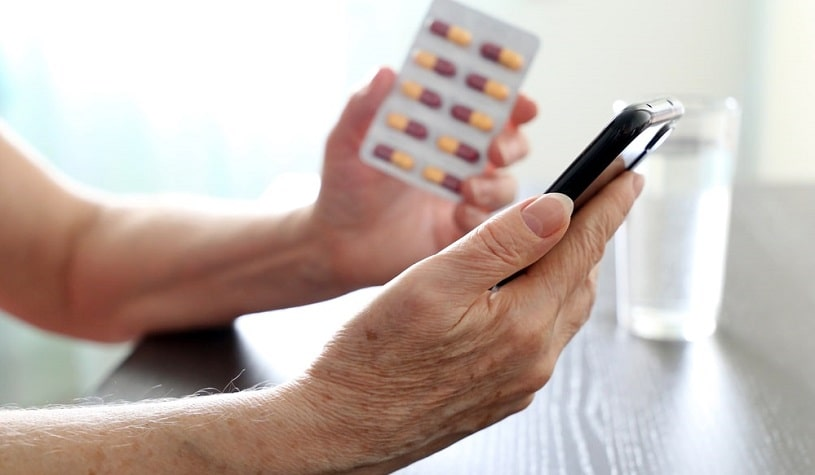 Man with smartphone and pills in hands reading about Valium duration.
