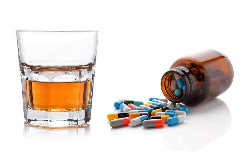 Glass of whisky and antibiotic pills.