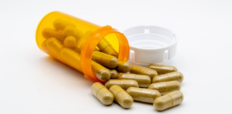 Green capsules of Kratom powder spilling out of an orange pill bottle.