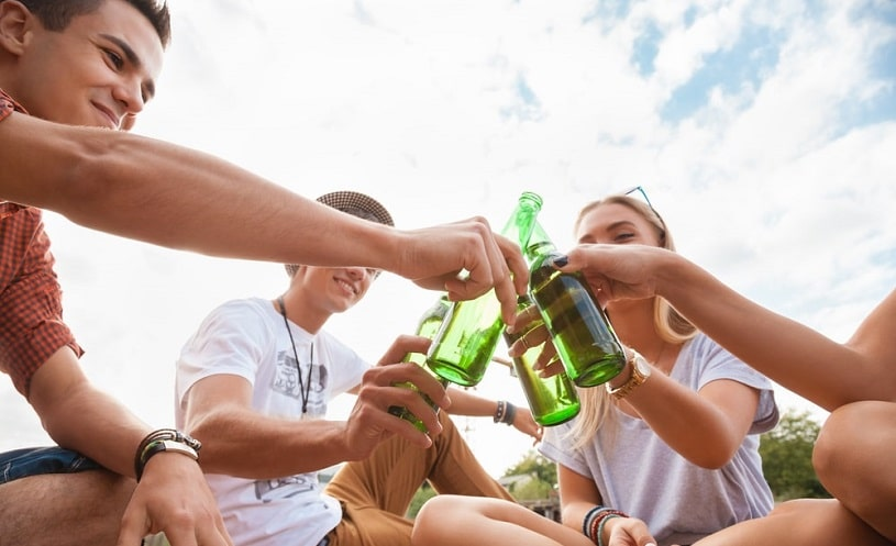 Teenagers drinking beer outdoors.
