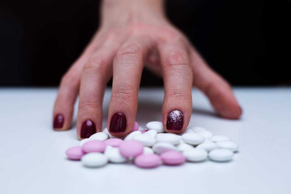 Hand surrounded by Prozac pills.