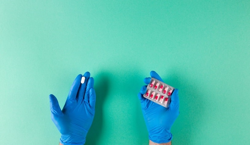 Hands in gloves holding Tramadol and Norco pills on green background.