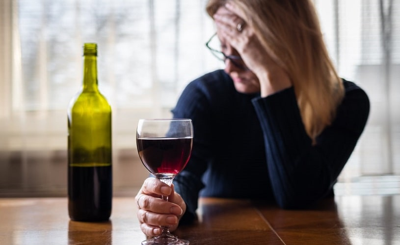 Sad and stressed woman drinking wine at home.