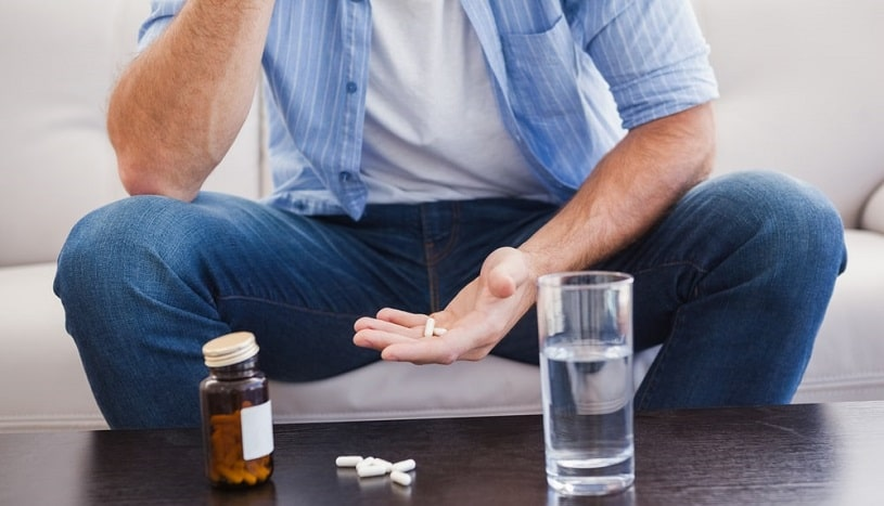 Man taking pills on the couch in the living room.