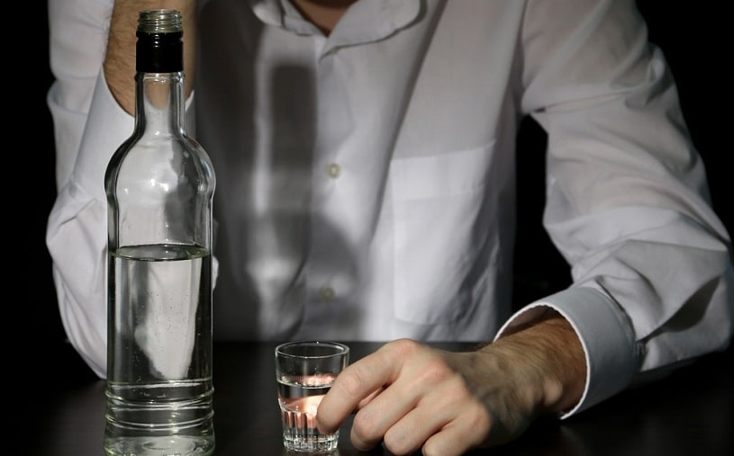 Man is drinking alcohol on black background.