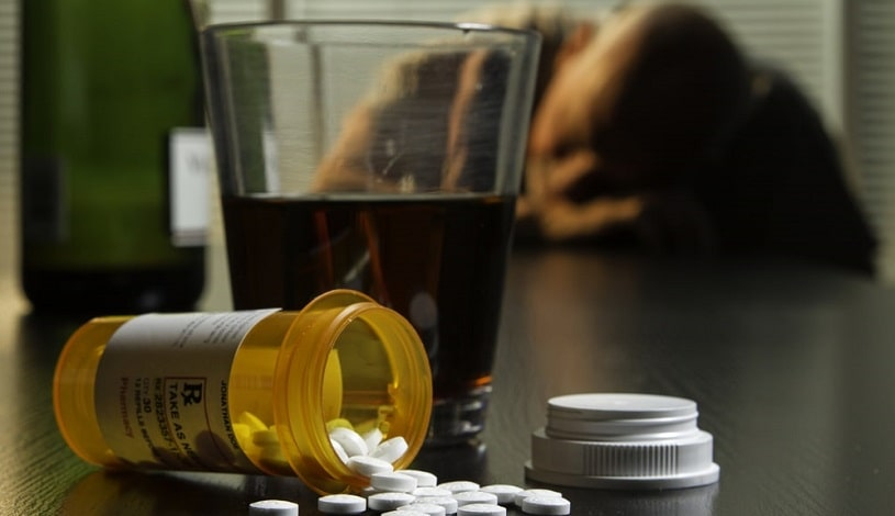 A man overdosed on Valium and alcohol, pills and alcohol on table.