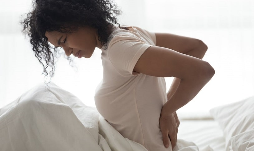 Sad young woman touching her back feeling pain.