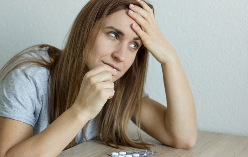 Sick ill depressed woman taking a pill.