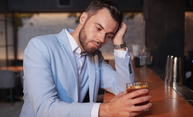 Depressed man drinking alone at a bar.