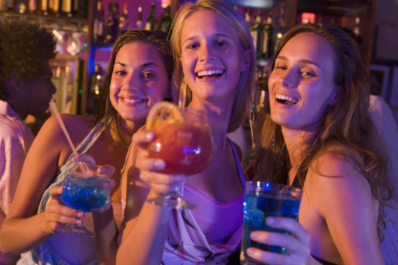 Women bingle drink in a club.