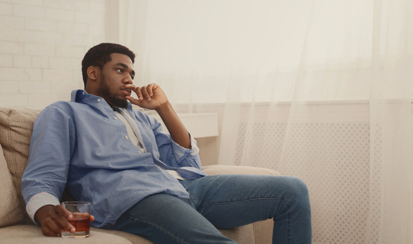 Depressed african-american man drinking alcohol at home.