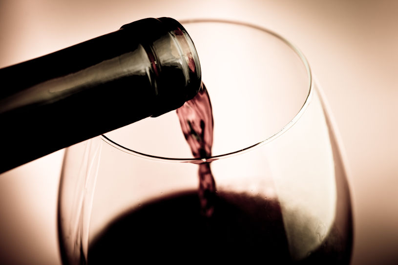 Pouring aged red wine in the glass.