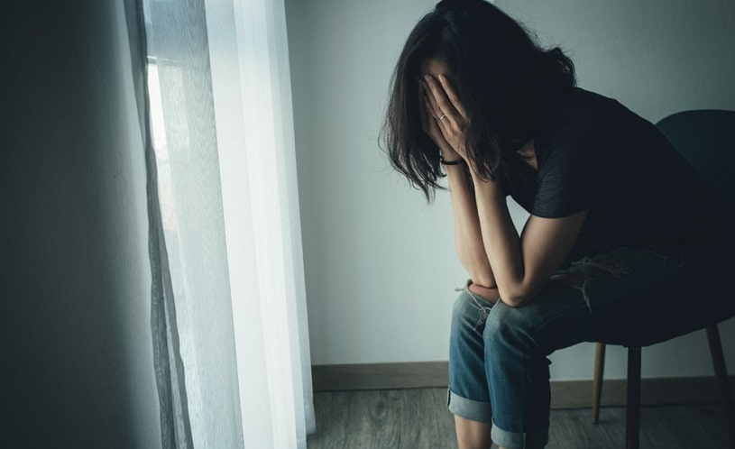 Young depressed woman sitting on the chair covering her face.