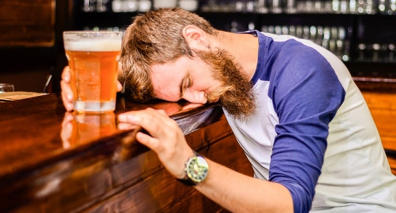Drunk man sleeps and holds a glass of beer.