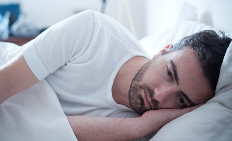 Depressed man experiencing pain lying in bed.