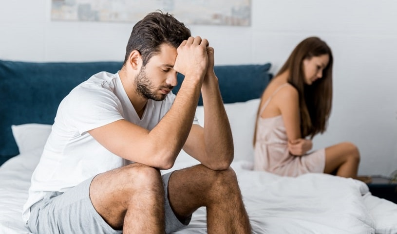 Depressed man sitting on bed with girlfriend after quarrel about sexual problems.