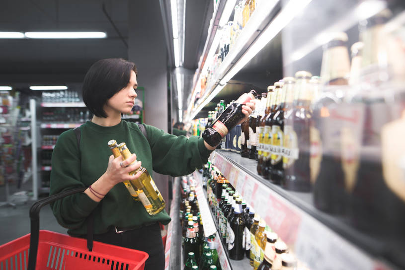 Girl takes alcoholic drinks in the supermarket.