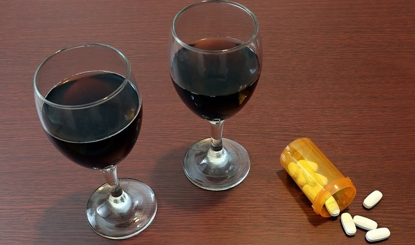Two glasses of red wine next to bottle of Klonopin tablets.