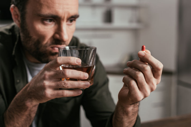 Man holding whiskey glass and pill.