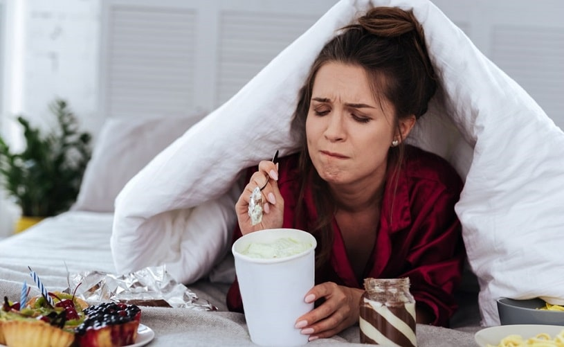 Depressed woman eating desserts in bed.