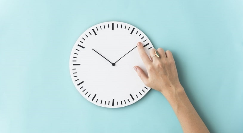 Clock and a hand on the blue background.