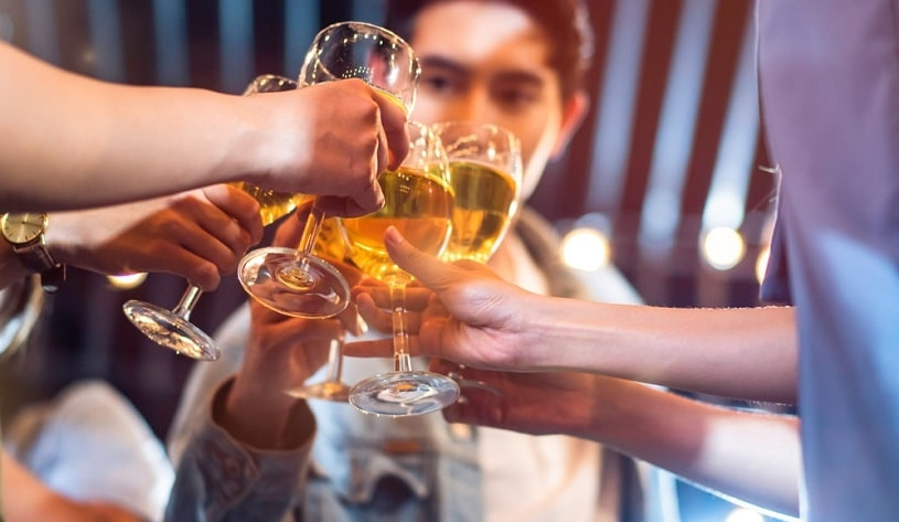 Friends celebrating and drinking at a social event.