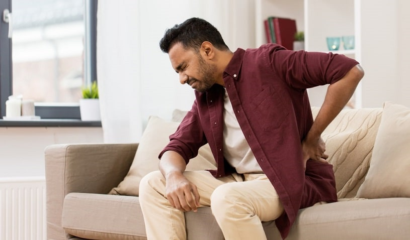 Man experiencing pain sitting on the couch at home.