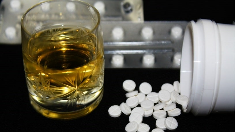Pills and a glass of alcohol.