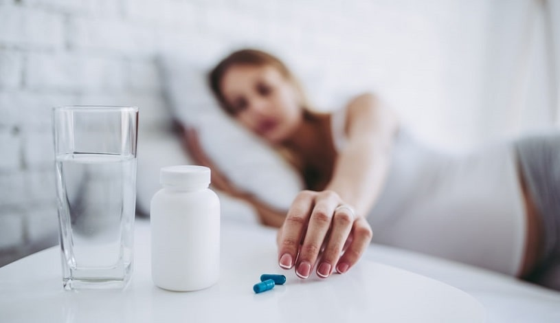 Sick woman lying in bed taking pills.