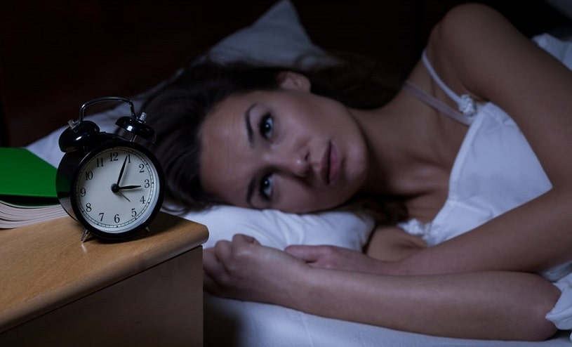 Woman with insomnia lying in bed.